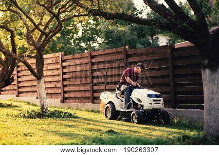 Man Using Lawn Tractor For Mowing Grass In Garden. Landscaping Works With Professional Tools
