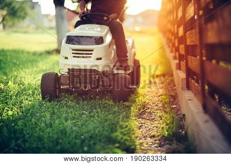 Close Up Details Of Landscaping And Gardening. Worker Riding Industrial Lawnmower