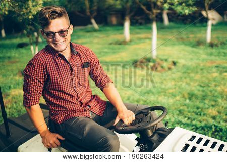 Portrait Of Man Working On Ride-on Lawn Mower Tractor