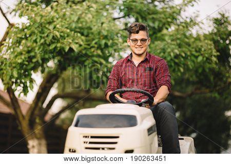 Backyard Lawncare Man Portrait - Smiling Worker Using Ride On Grass Mower