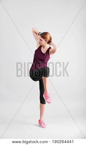 Beautiful woman doing bicycle crunch on light background