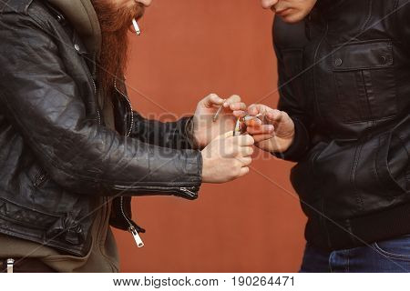 Two men smoking weed outdoors on color background