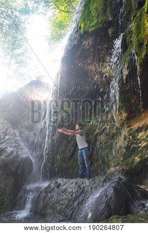 Man in wild nature. Man under a waterfall. Happy hiker under a small waterfall in mountains