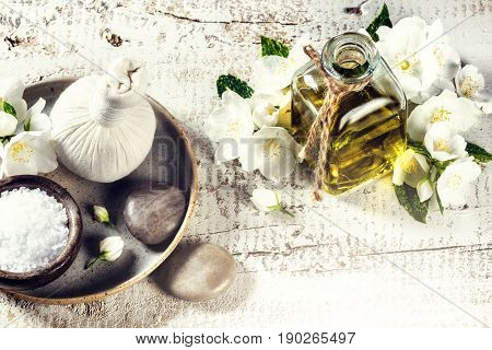 Spa setting with jasmine flowers and essential oil over old wood background. Wellness concept top view