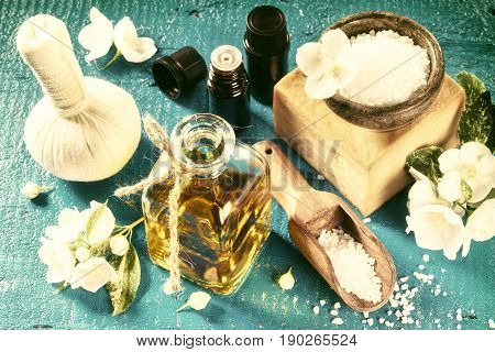 Spa setting with jasmine flowers and essential oil over old blue wood background. Wellness concept top view