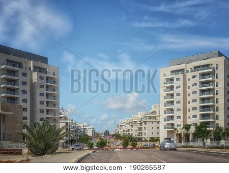 Nes Ziona Israel-March 20 2016: Front view of two white gray new 8 story residential buildings are located on both sides of the beginning of Khoshen street. Wide road and blue sky. Horizontal shot