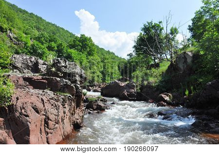 Beautiful view of mountain river in summer, Old Mountain, Serbia. Wild river with a lot of cascade in green rain forest
