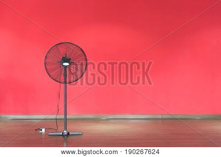 Black Metal electric fan isolated on red background.