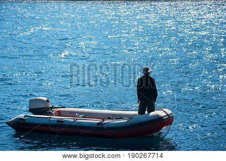 Crew standing on dinghy boat mooring on ocean with Calm and smooth sea in tropical island waiting for scuba divers.