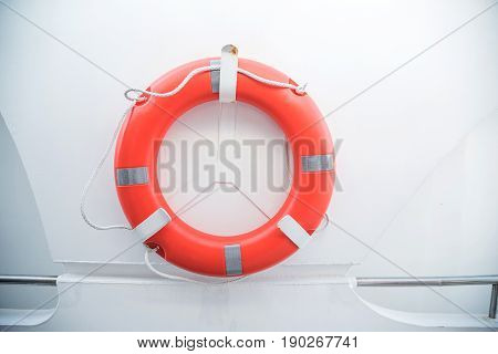 An orange life buoy for safety at sea attached to the cruise ship on white background and copy space.