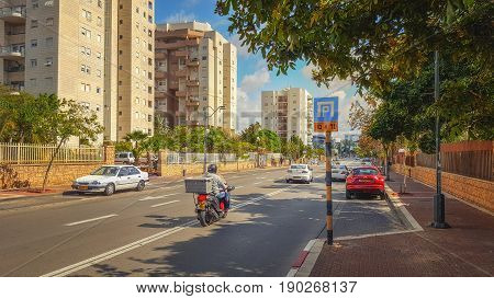 Rishon LeZion, Israel-April 14, 2016: View of urban road with some cars along multi-story modern condominiums are located at Ha-Shira Ha-Ivrit Street. Back of unidentified motorcyclist carrying a cargo in plastic box is seen in the center. There are green