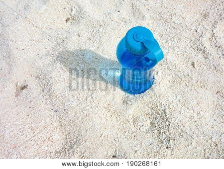 Top view of plastic reusable water bottle or blue canteen on the beach on a hot summer day. Background and copy space.