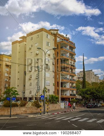 Rishon LeZion Israel-February 20 2016: View of renovated residential 8 story building under blue sky. Exterior balconies were built to the condominium. Facade was painted in beige brown color. It is located at 32 HaPardes HaRishon Street. Vertical shot