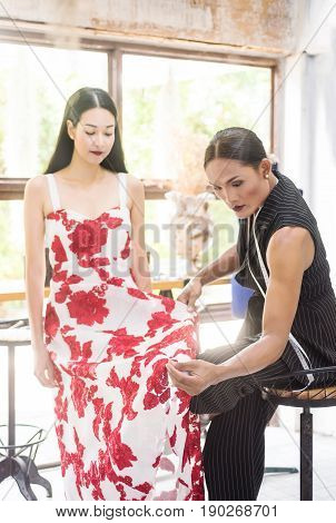 Young Asian transgender or transvestite tailor measuring client for custom made garment. Fashion designer stylish showroom concept.