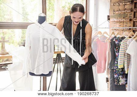 Young Asian transgender or transvestite tailor measuring white shirt for custom made garment. Fashion designer stylish showroom concept.