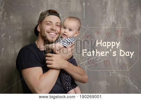 Daddy with cute baby daughter and text HAPPY FATHER'S DAY on grunge background