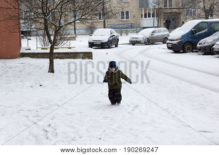 warm winter dressed boy playing on a snowy street