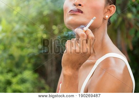 Close up of Asian transwoman or transgender holding cigarette and smoking in garden. People smoking and bad habits concept. Picture for World No Tobacco Day. Background or copy space.