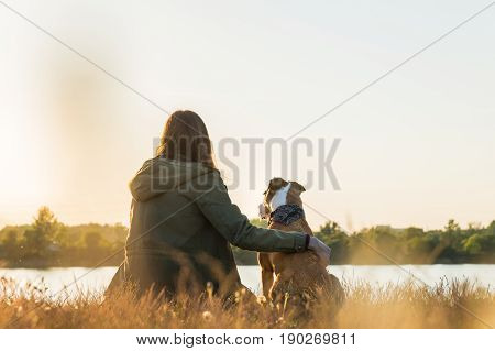 Young woman and dog enjoy nature sight at dawn near the lake. Female person in parka and staffordshire terrier puppy sit at sunset near the river and look in distance