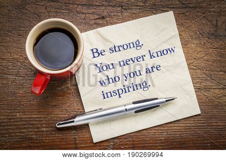 Be strong. You never know who you are inspiring. Inspirational handwriting on a napkin with a cup of coffee.