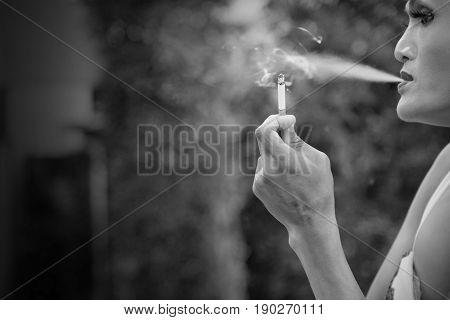 Black and white close up of Asian transwoman or transgender holding cigarette and smoking in garden. People smoking and bad habits concept. Picture for World No Tobacco Day. Background or copy space.