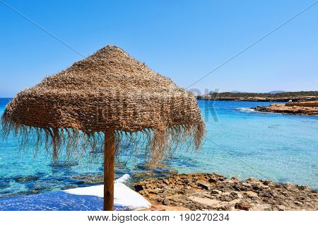 detail of a relaxing area in a beach in Ibiza, Spain, with a comfortable sunlounger and a rustic umbrella made of natural fibers