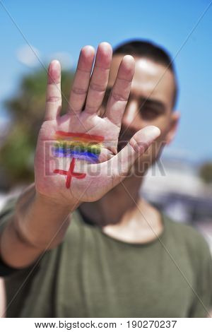 closeup of the a young caucasian man with a rainbow flag painted and a plus sign painted in the palm of his hand, for the LGBTI HIV-positive people