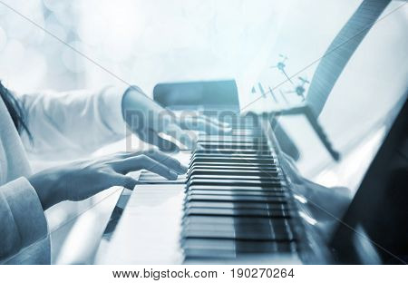 Close up of pre teen girl pianist practicing on an upright piano with classical music soft focus with blue tone and bokeh blur background)