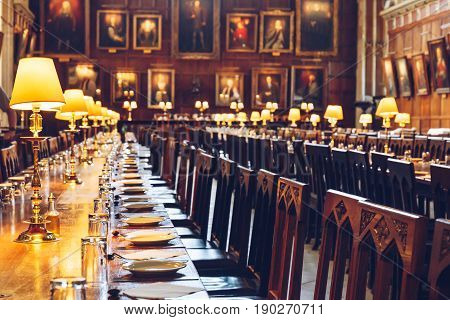 OXFORD, UK - MAY 22, 2017: Table set for dinner at The Great Hall of Christ Church, University of Oxford. The Hall was replicated at film studios as the grand dining hall at Harry Potter's Hogwarts school.