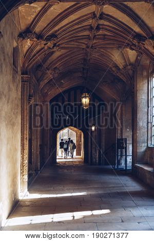 OXFORD, UK - MAY 22, 2017: Students walk down the corridor in Christ Church College, one of the largest colleges of the University of Oxford, England.