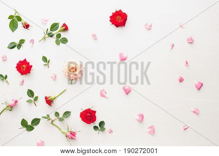 Flowers and petals background  made of pink and red roses, green leaves and pansy flowers on white background. Flat lay, top view