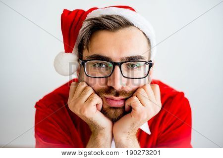 A portrait of a bored Santa Claus sitting at a table