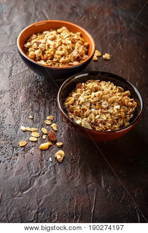 Delicious homemade granola or muesli in two ceramic bowls on stone background.