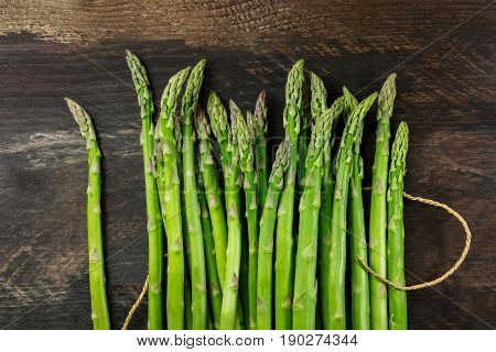 An overhead photo of fresh asparagus stalks with a piece of jute, a rustic background with a place for text