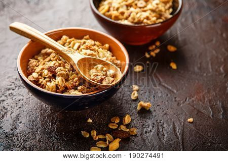 Delicious homemade granola or muesli inwppden spoon on stone background. . Place for text.