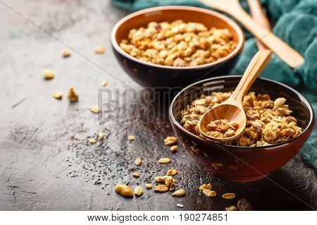 Delicious homemade granola or muesli in two ceramic bowls with wppden spoon on stone background. Place for text.