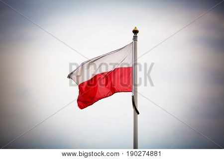 Lonely flag of Poland on a pole - dark mood of solitude and isolation