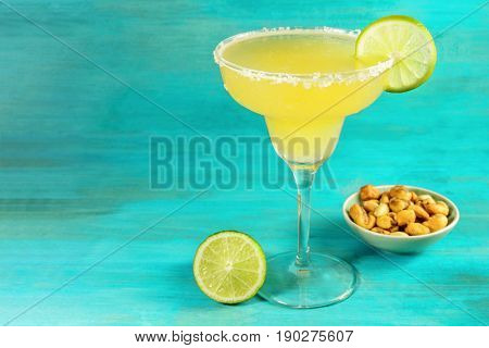 A photo of a lemon Margarita cocktail with wedges of lime and a salted nuts snack, with a place for text
