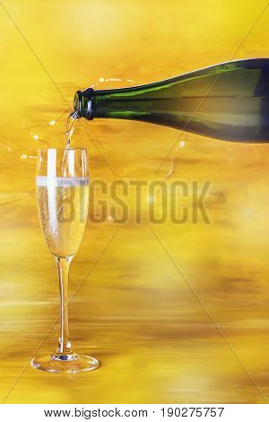 Champagne being poured into a flute glass on a blurred golden background with shining lights, with a place for text