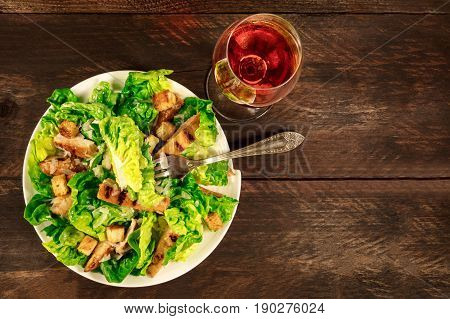 An overhead photo of a plate of chicken Caesar salad with a glass of rose wine, on a dark rustic texture with copy space