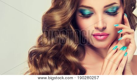 Woman with turquoise   manicure nail . Girl with  blue nail Polish on the nails . Makeup and cosmetics