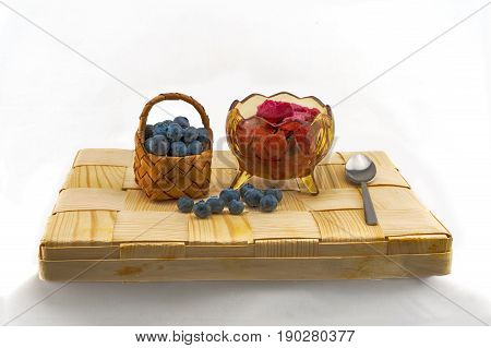 bilberry and bilberry ice cream on a wattled wooden tray