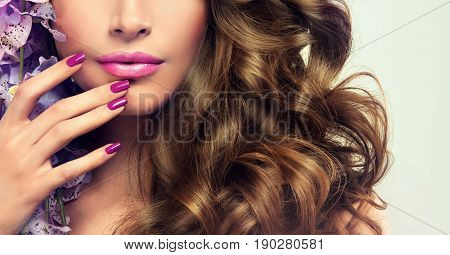 Woman with purple  manicure nail . Girl with violet  nail Polish on the nails . Makeup and cosmetics