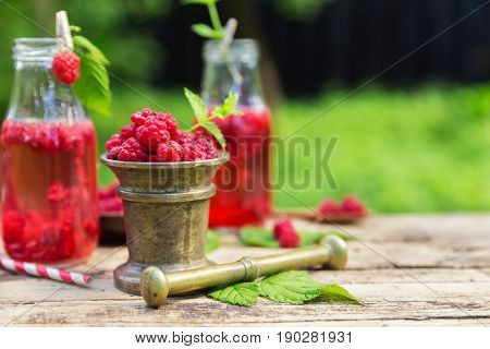 Grinding raspberries with a mortar and pestle making juicy smoothie drink in garden