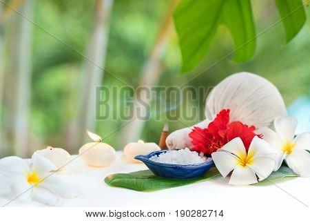 Spa concept herb salt and plumeria flowers on tropic leaf background
