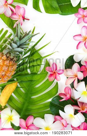 Tropic flat lay top view tropical summer botanical concept with banana pineapple fruits palm leaves and plumeria on white