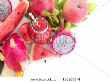 Tropic flat lay top view tropical summer concept with pink tropical watermelon apple dragon fruits and smoothie juice palm leaves and plumeria on white