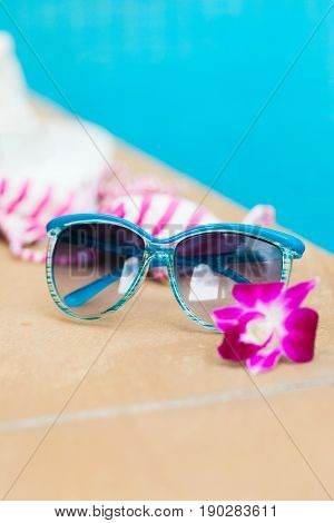 Sunglasses orchid flower and colorful swimwear near swimming pool