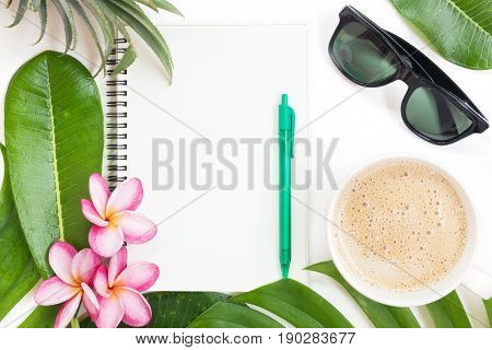 Tropic flat lay top view tropical botanical summer concept with note book sunglasses coffee cup pineapple palm leaves and plumeria on white