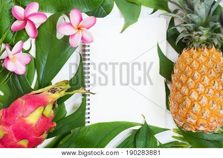 Tropic flat lay top view tropical summer botanical concept with pineapple dragon fruits palm leaves and plumeria on white